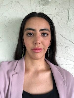 Woman in a light pink blazer looking into camera with a straight face.