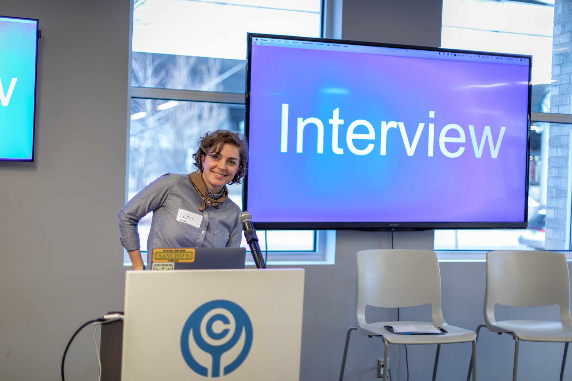 """Woman in front of a screen that reads """"Interview"""""""