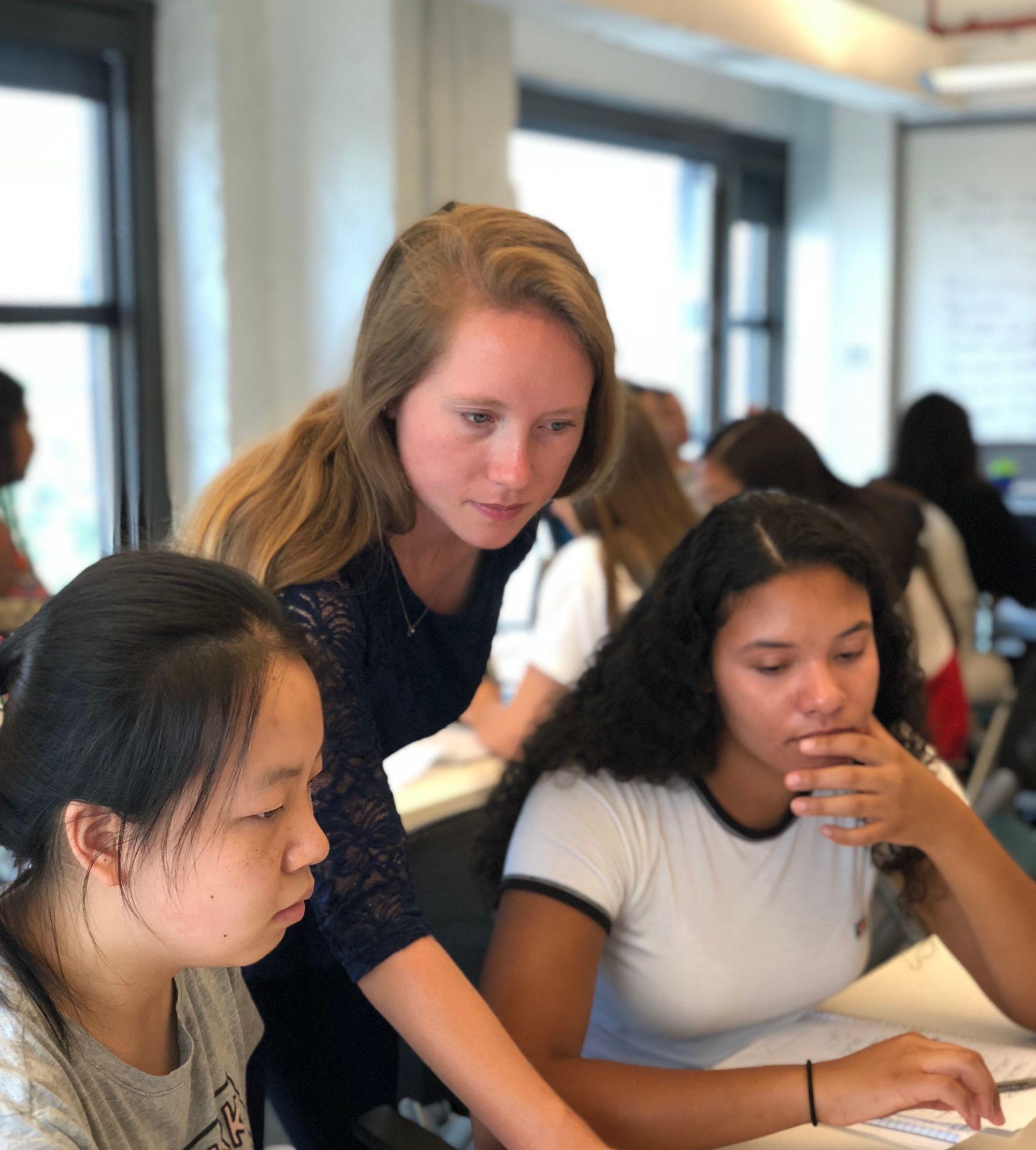 Woman teaching two girls in classroom.