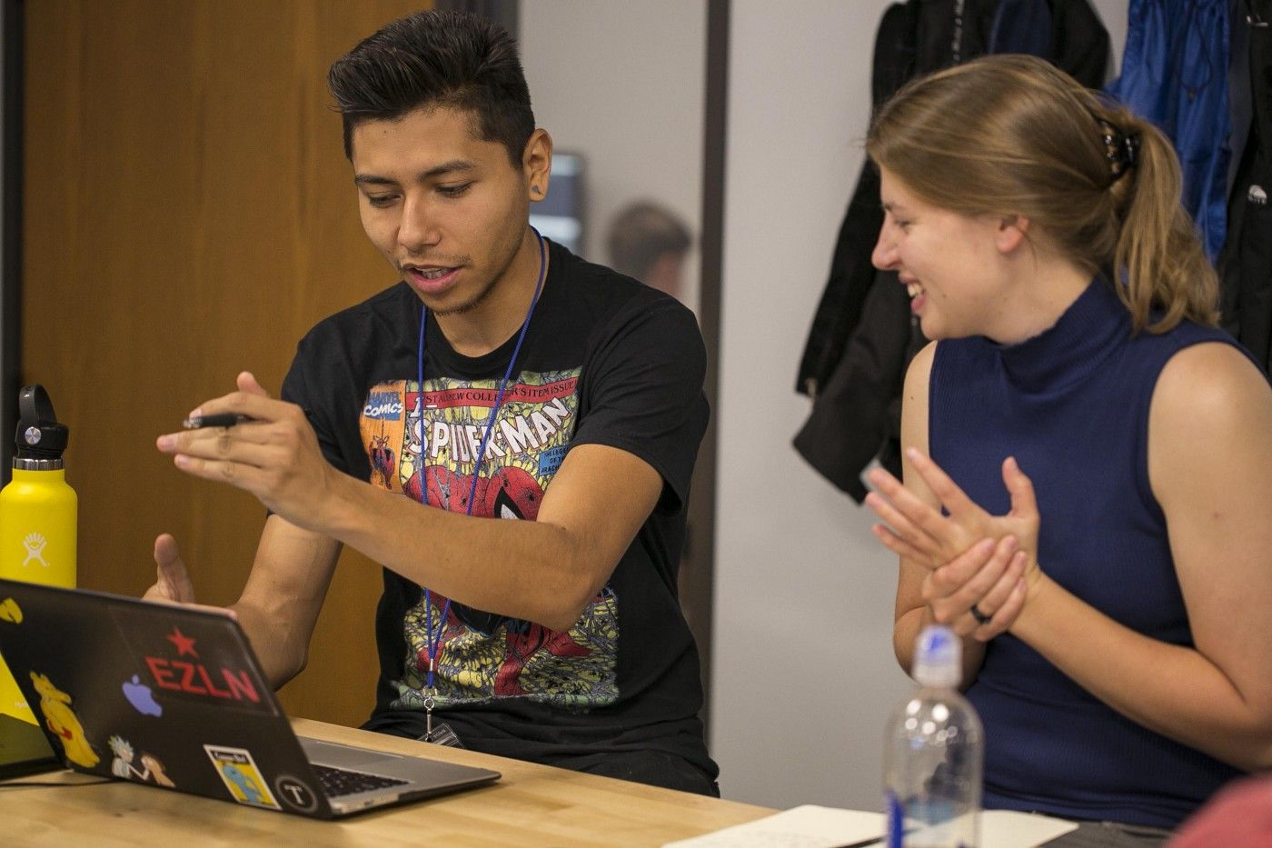 A man and a woman are animatedly talking together while looking onto the same laptop screen.