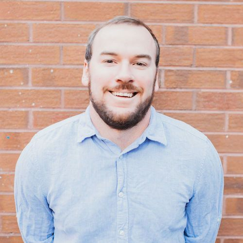 Man standing in front of a brick wall and smiling.